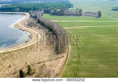 Bicycle Lane Between Green Fields, Trees And Lake In Sunny Spring Day. Aerial Photography