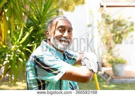 Senior African American man spending time in the garden, smiling and looking straight into a camera. Social distancing and self isolation in quarantine lockdown.