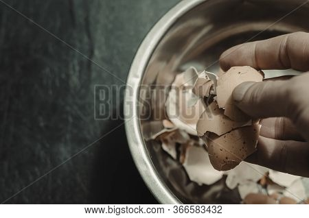 A Male Hand Dips Eggshells In A Metal Bowl. A Metal Bowl With Eggshell On A Black Background. Adult