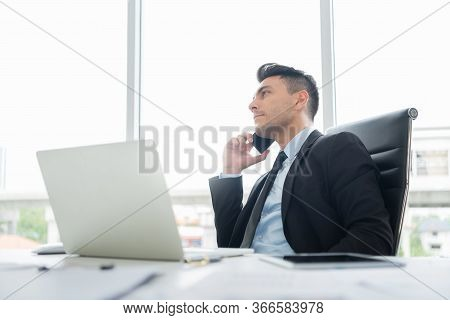 Smart Handsome Businessman In Black Suit Is Sitting Using A Mobile Phone For Negotiating Business De