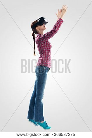 Young Woman Wearing Virtual Reality Glasses Against Gray Background. Beautiful Woman In Checkered Sh