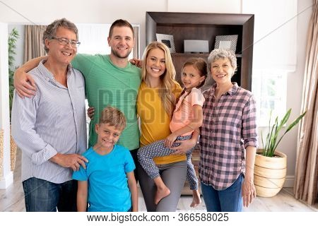 Portrait of a three generation Caucasian family spending time together at home, standing in the sitting room, smiling and looking straight into a camera.
