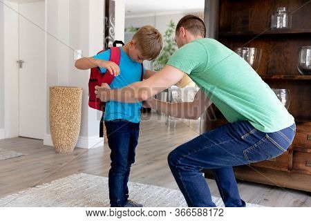 Caucasian man wearing a green t-shirt helping his son wearing a red rucksack preparing for leaving to school.