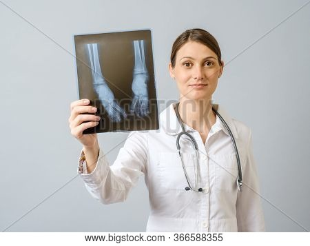 Female Doctor Examining X-ray Image Of Legs Of Newborn Baby. Isolated Over Gray Background