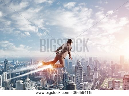 Businessman In Suit And Aviator Hat Flying In Blue Sky As Superhero. Business Person As Superhero Wi