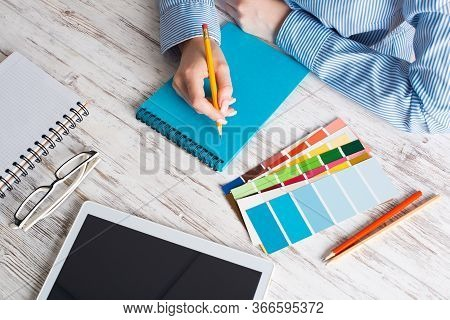 Top View Creative Designer Writing In Notebook At Vintage Wooden Desk. Office Workplace With Tablet