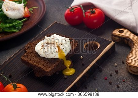 Poached Egg On Whole Grain Bread On A Dark Background. The Yolk Stretches From A Boiled Egg To A Woo