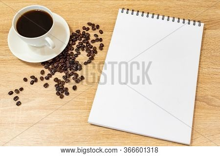Coffee Grains On A Wooden Table, Instant Coffee On The Surface, Background For Advertising, Notebook