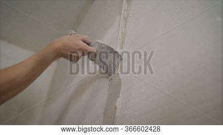 Worker Spreads Mortar On The Wall. Wall Repair In A New Apartment. Hand Of Worker With Plaster And T