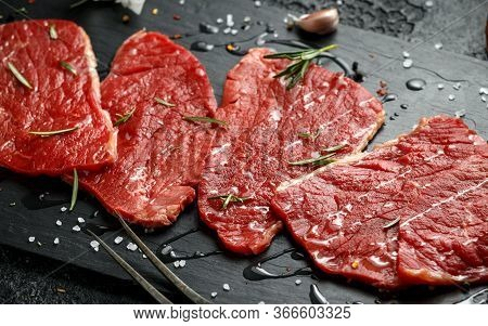 Raw Fresh Sizzling Beef Steak With Herbs On Stone Board