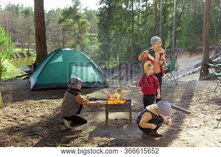 Children Near A Fire In The Forest On The Background Of The Tent, Camping, Travel, Tourism, Hike And