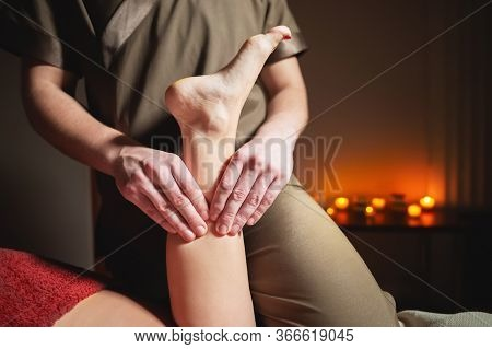 Close-up Professional Calf Muscle Massage To A Female Client By A Male Physiotherapist In A Massage
