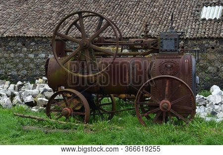 Farm With A Rusty Old Steam Tractor Resting In Rubble.