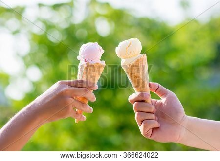 Woman Holding And Eating Ice Cream In The Park. Hands Holding Melting Ice Cream Waffle Cone In Hand