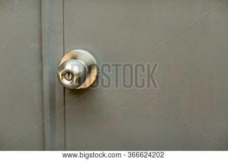 Door With Grill, Stainless Door Knob Or Handle On Wooden Door In Beautiful Lighting.a Handle On A Do