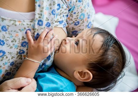Woman Breast Feeding Her Baby On Light Background. Mother Holding Her Newborn Child. Mom Nursing Bab