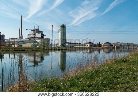 Green Energy And Industry With Hydropower And River. Power Plant On The Water With Blue Sky And Gree