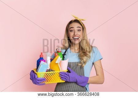 Start Of House Cleaning. Happy Housewife With Basket With Cleaning Supplies Isolated On Pink Backgro