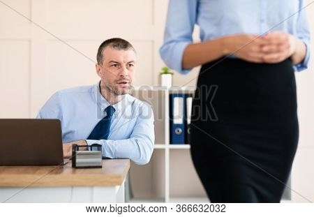 Sexual Harassment. Lustful Businessman Staring At Colleague Womans Butt Sitting At Workplace In Mode
