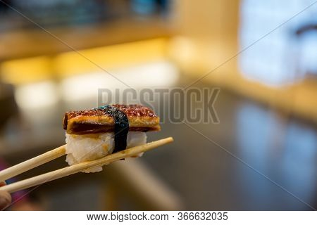 Close Up Chopsticks Hold On Sushi Freshwater Eel Grilled. Japanese Food For Healthy. Unagi Sushi, Pr
