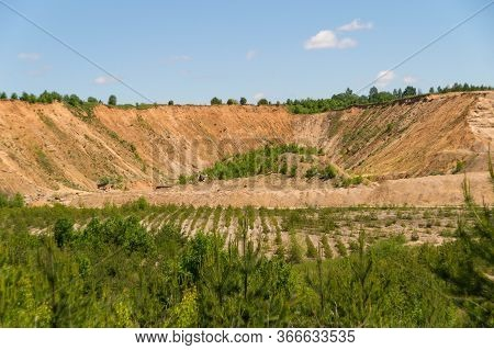 Landscape: Inactive Abandoned Overgrown Sand Quarry Under A Blue Sky