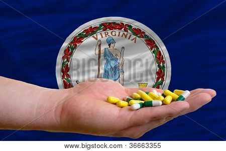 Holding Pills In Hand In Front Of Virginia Us State Flag
