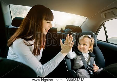 Pretty Young Woman Mother Takes Care About Her Little Daughter In A Car Safety Seat, Sitting Togethe