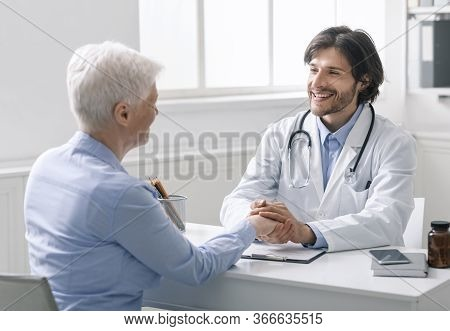 Medical Empathy Concept. Caring Doctor Holding Hand Of Senior Woman At Visit