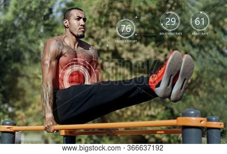 Outdoor Strength Training. Muscular African American Guy Doing Abs Exercises On Parallel Bars At Spo