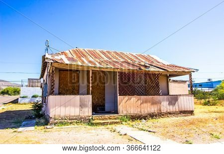 Abandoned Corner Home With Rusty Tin Roof & Boarded Up Windows