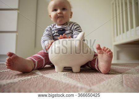 Low Angle View Of A Baby With A Piggy Bank Savings Box. Childcare Costs