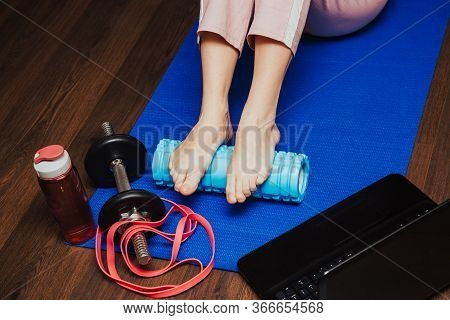 Varsity Athlete Using A Foam Roller To Release Her Tight Muscles. Home Fitness, Home Massage
