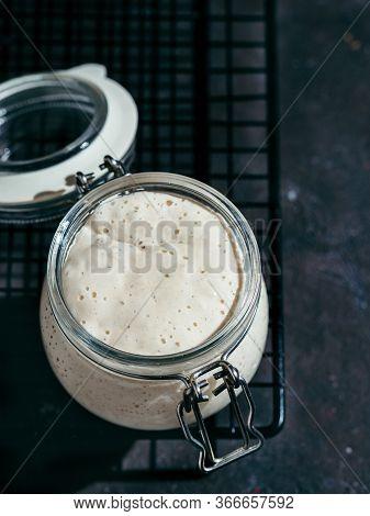 Wheat Sourdough Starter. Glass Jar With Sourdough Starter On Dark Background, Copy Space. Vertical.