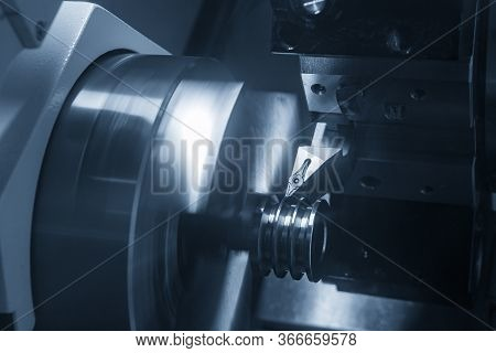 The Cnc Lathe Machine Groove Cutting The Metal Pulley Parts With Lighting Effect. The Hi-technology