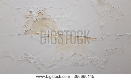 Old Stucco Wall With Flaking Paint And Yellow Surface Damaged By Humidity. Building Wall Needed Repa