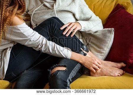 The Girl And The Guy Are Sitting On The Couch, Hugging Each Other. Close-up Without Faces. The Conce