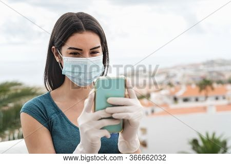 Young Woman Wearing Surgical Face Mask Using Mobile Smartphone On Home Terrace - Girl In Quarantine