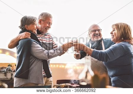 Happy Senior Friends Drinking Red Wine At Barbecue On House Patio - Mature People Cheering And Dinin