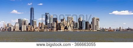 Panorama of Lower Manhattan of New York City with USA Flag from liberty island. This also known as Downtown Manhattan or Downtown New York the largest business district in state of New York and USA.