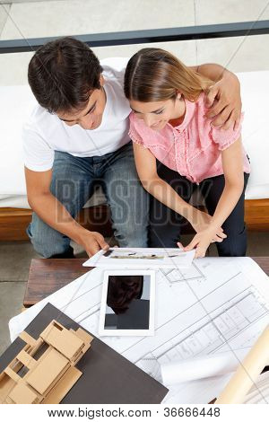 High angle view of young couple looking at house plans with tablet PC, blueprint and model structure on table