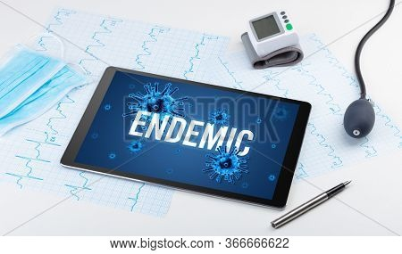 Tablet pc and doctor tools on white surface with ENDEMIC inscription, pandemic concept