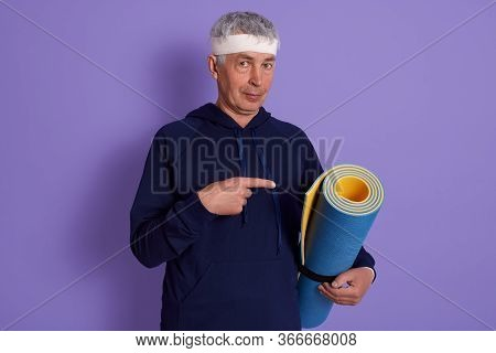 Indoor Shot Of Elderly Man Wearing Sport Clothing, Holding Yoga Mat In Hand And Pointing At It With