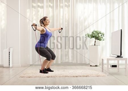 Full length shot of a young female exercising with a resistance band while watching tv