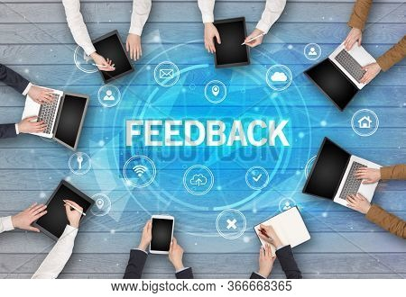 Group of people having a meeting with FEEDBACK insciption, social networking concept