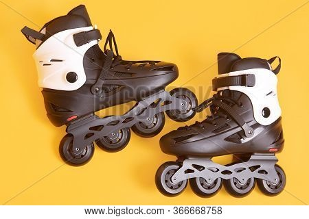 Close Up Portrait Of Adult Rolling Skates Isolated Over Yellow Studio Background, White And Black Ro