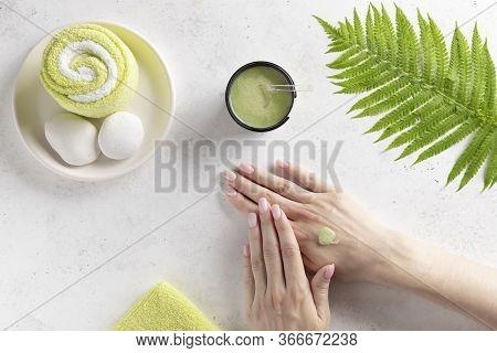 Woman Applying Natural Scrub To Her Hand. Hand Massage, Skin Exfoliation. White Background With Fern
