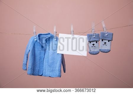 Baby Top And Socks Pegged On A Line With A Blank White Card