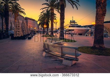 Early Dawn Cityscape With Restaurants, Street Cafes In The Touristic Harbor. Anchored Yachts In The