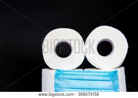 Toilet Paper Rolls With A Medical Mask Folded In The Form Of An Emoticon, On A Black Background. Con