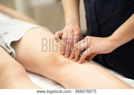 Physiotherapist Woman Doing A Treatment On A Womans Knee.